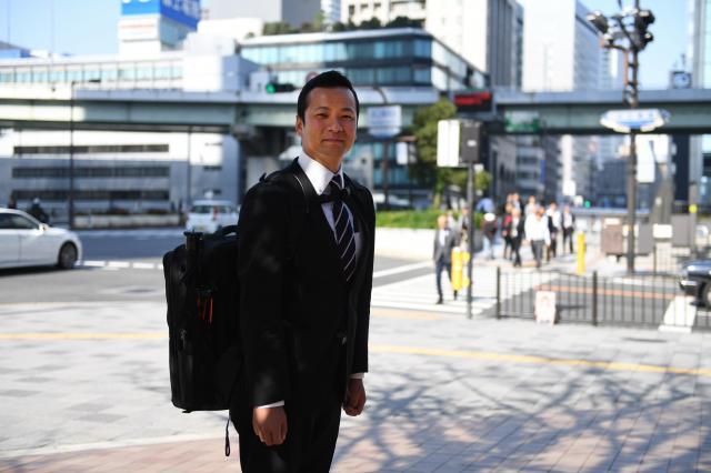 関西出張に来ていた竹内圭さん。仕事の合間に女子車いすバスケットボールの試合を撮影したため、待ち合わせ場所にはスーツにカメラバッグを背負って現れた=2016年11月7日午後、大阪市北区、井手さゆり撮影