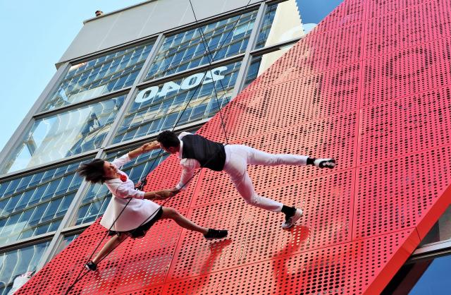 ビルの壁面が地上であるかのように軽やかなダンスをするバンダループ=東京・原宿