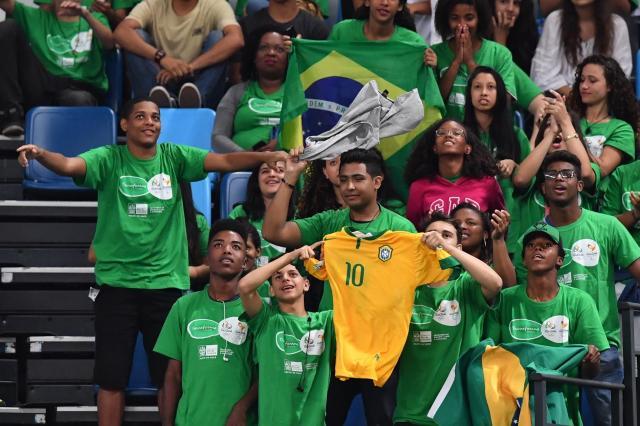 車いすラグビーの日本―アメリカ戦を観戦するブラジルの子どもたち。サッカーブラジル代表のユニホームとブラジル国旗は、どの競技会場でも見かけた=2016年9月16日、カリオカアリーナ、井手さゆり撮影