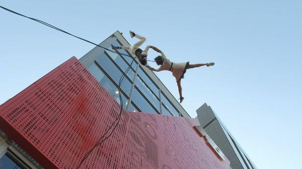 ビルの壁面が地上であるかのように軽やかなダンスをするバンダループ=東京・原宿、佐藤正人撮影
