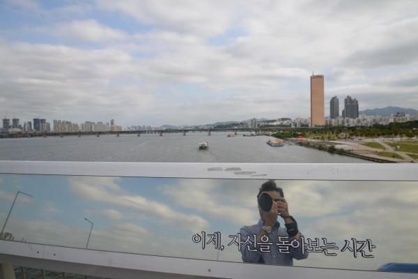 麻浦大橋の欄干は、自分の姿が映り込むように鏡状になっている。自殺を防ぐため、ハングルで「いま、自分を振り返る時間」と書かれている=ソウル、神谷毅撮影