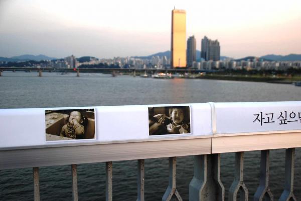 麻浦大橋の欄干に設置されたメッセージ板。身近な家族を思い出すようにと、子どもの写真が貼られている=2012年