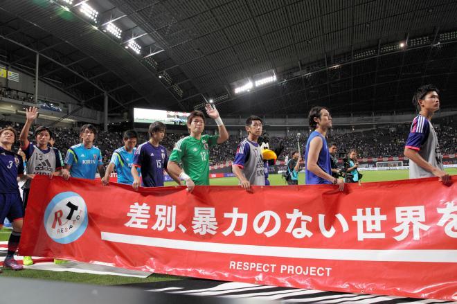 差別反対の横断幕を掲げサポーターらにあいさつする日本代表の選手たち=2014年9月5日、杉本康弘撮影