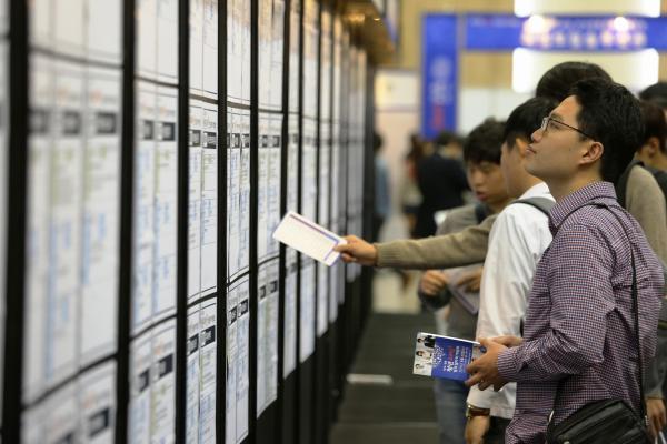 韓国の就職説明会。学生たちが企業の採用情報の掲示板を真剣な表情で見ていた=2015年、大邱、東岡徹撮影