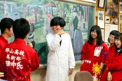 部員とおしゃべりする浜崎先生。部活動中、部員たちは赤いつなぎを着ています