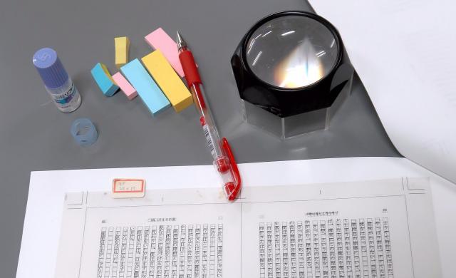 丸山さんの愛用品。細かい文字のルビを確かめるためのルーペや、用途別に使い分けるふせん、目薬など=東京都新宿区矢来町の新潮社