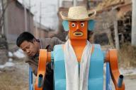 ロボットが引くリアカーに乗る呉玉禄さん=2009年1月、北京郊外