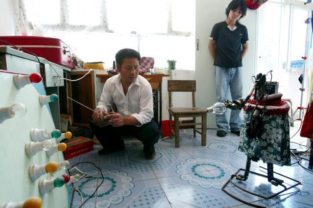 リモコンで「呉老五」に電球をインストールさせる呉玉禄さん。横にいるのはロボット作りを手伝う次男=2003年9月、北京郊外