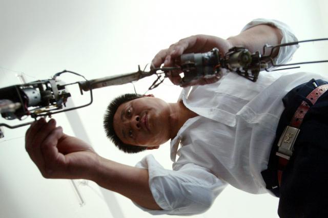 自宅でロボットの部品を微調整する呉玉禄さん=2003年9月、北京郊外