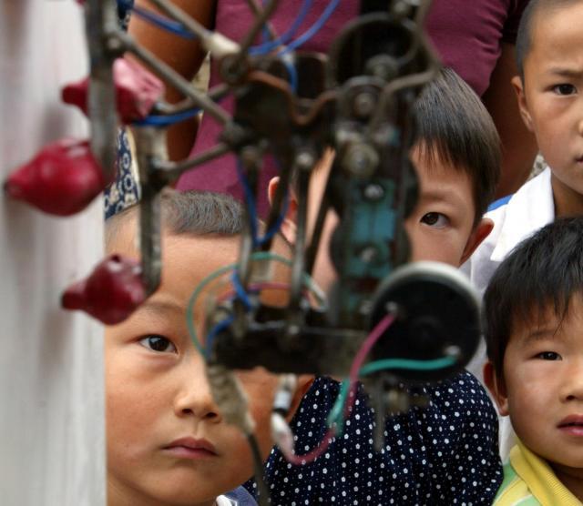 壁を登るロボットをじっと見つめる子どもたち=2003年9月、北京郊外)