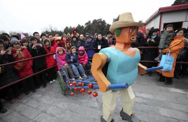 旧正月に子どもたちをリアカーで引くロボット「呉老三十二」=2010年2月、北京地壇公園