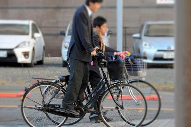 駅前の平らな道でも立ちこぎするサドル低い族の男子高校生(手前)=福井市