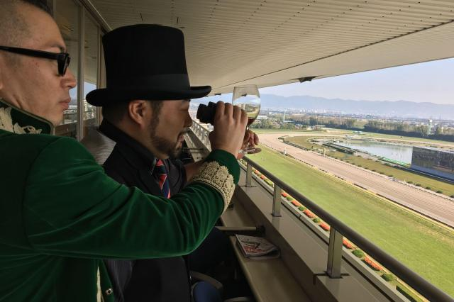 ワイングラス越し、真剣な表情で競馬観戦する髭男爵の2人=サンミュージック提供