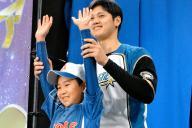 「応援大使」の抽選で、自らを引き当てた月形町の男の子の手を掲げる大谷=2016年11月23日、札幌ドーム