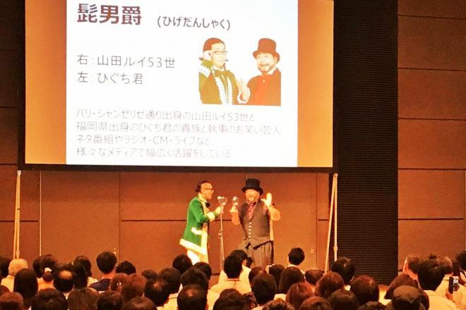 普段とは違う巨大な会議室。プロジェクターに映されたプロフィールの前でネタを披露する髭男爵の2人=サンミュージック提供