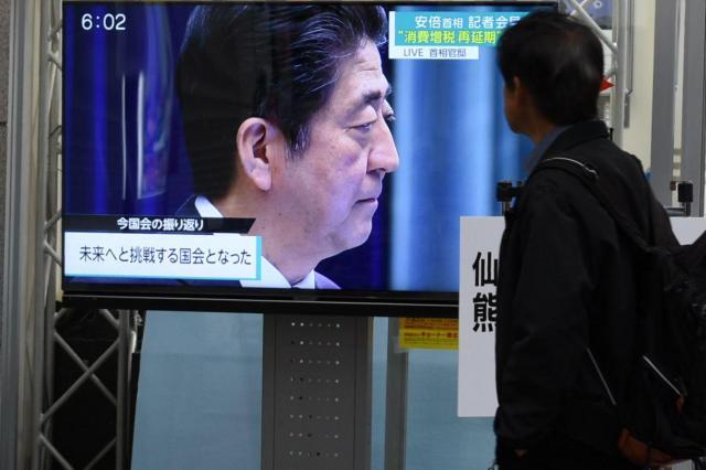 テレビで安倍首相の記者会見を見つめる男性=2016年6月1日、仙台市青葉区