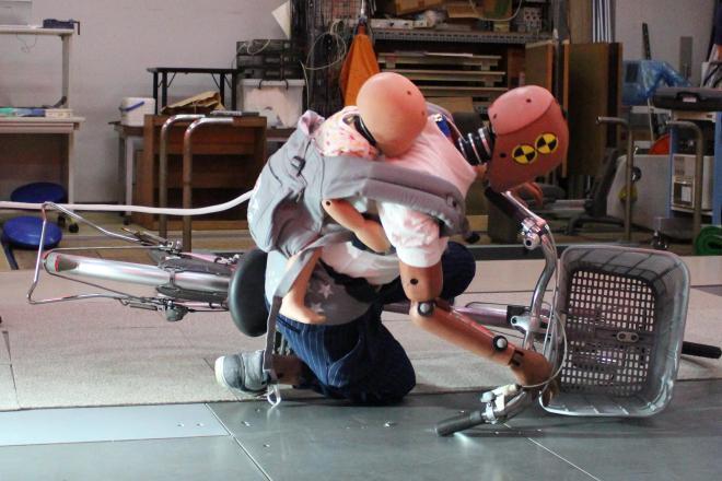 「おんぶ自転車」の転倒実験で倒れるダミー人形=東京都目黒区の東京工業大学