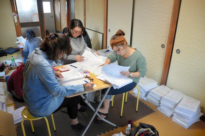集計作業をするメンバーら。関西のファンを中心に常時10人程度集まったという=兵庫県尼崎市