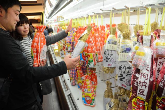 わら納豆を手に取る買い物客=2016年2月11日、茨城県笠間市の常磐自動車道上り線の友部サービスエリア、福地慶太郎撮影