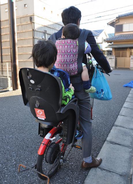 練馬区の男性に「おんぶ自転車」をしていた頃の様子を再現してもらった。着替えのほか、保育園で使うシーツをいれたバッグをハンドルにかける日も=東京都練馬区 ※安全に十分に配慮した上で撮影しています。おんぶ自転車の状況の再現で、実際にこのような状態での登園はしていません