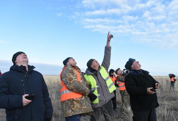 空に舞うソユーズを見つけ、指さすロシアのツアー会社の担当者=2016年10月30日午前、カザフスタン、竹花徹朗撮影