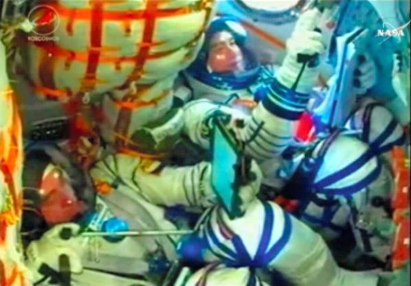 打ち上げ後、ソユーズ宇宙船の中で機器の確認をする大西卓哉宇宙飛行士(右)=NASAテレビから