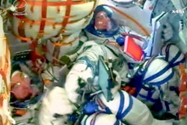 打ち上げられたロケットが軌道投入に成功し、ソユーズ宇宙船内で船長(手前)と手を合わせて喜ぶ大西卓哉宇宙飛行士=NASAテレビから