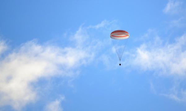 パラシュートを開いて地球に帰還するソユーズ=2016年10月30日午前9時55分、カザフスタン、竹花徹朗撮影