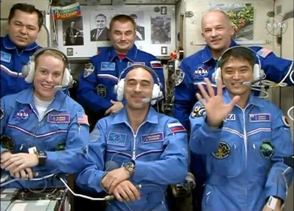 ISSに乗り込み、地上との会話中に手を振る大西卓哉さん(前列右端)=NASAテレビから
