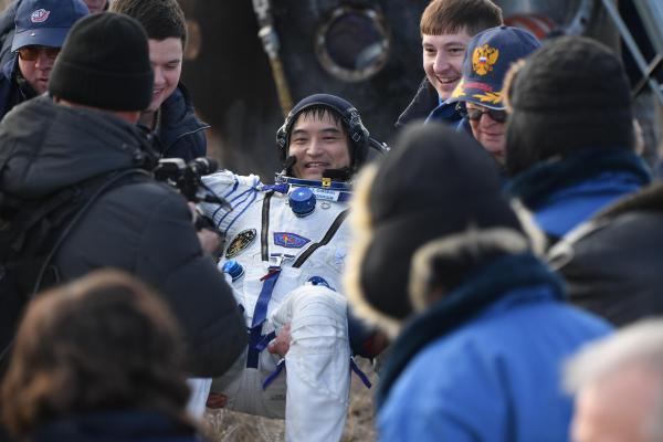 地球に帰還し笑顔をみせる宇宙飛行士の大西卓哉さん。後方は着陸したソユーズ=2016年10月30日午前、カザフスタン、竹花徹朗撮影