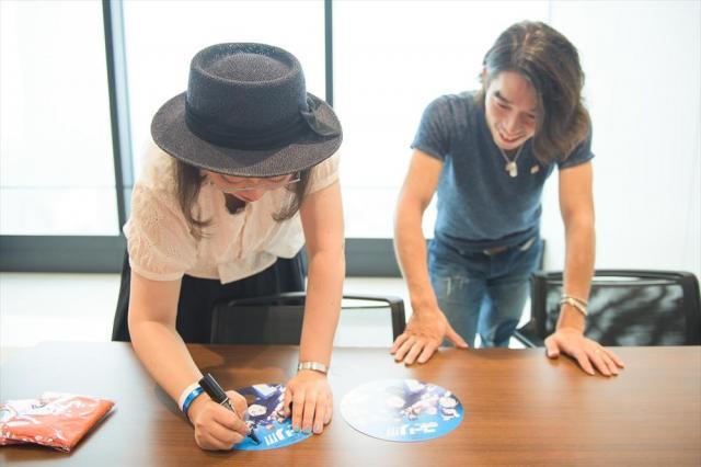 サインを書く久保ミツロウさん(左)と、無良崇人選手