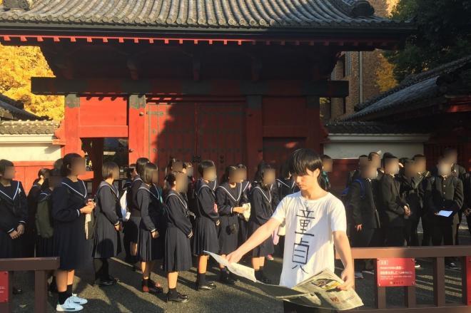 修学旅行生に囲まれながら、「童貞」と書かれたTシャツを着て、東大・赤門前でかっこよく新聞を読む高野りょーすけさん
