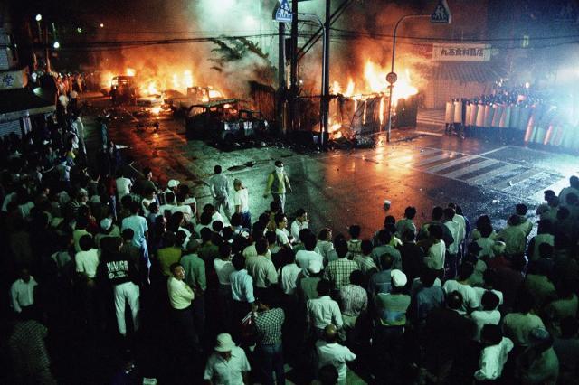 暴動で、機動隊(右奥)に石や空き瓶を投げる群衆と燃える車=1990年、大阪市西成区