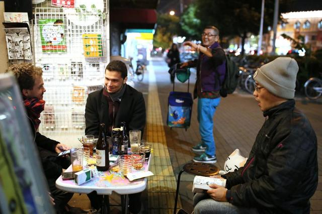 ネコのぬいぐるみを置いていった通りすがりの男性(右奥)=大阪市西成区