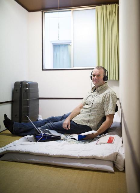 1泊1700円、広さ3畳の部屋に3カ月滞在予定だというオランダ人の男性=大阪市西成区