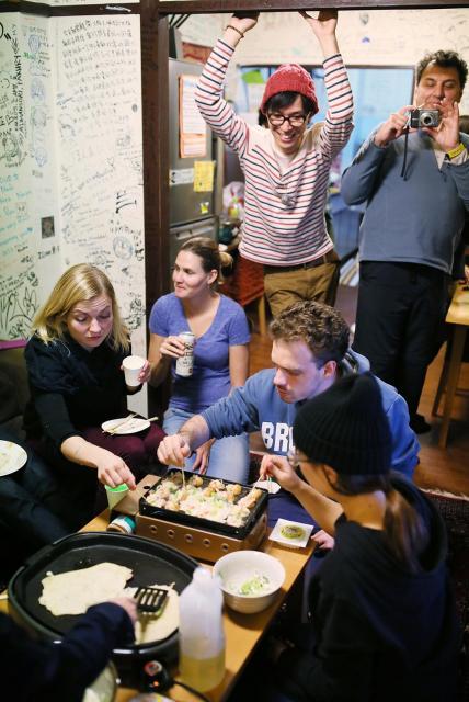 簡易宿所を改装した宿で、日本人スタッフとタコ焼きパーティーをする外国人旅行者。壁には寄せ書きがびっしり=大阪市西成区