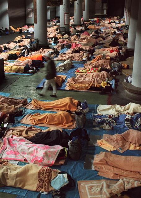 支援団体の要求に応じ、開放されたあいりん総合福祉センターの1階。冷え込んだクリスマス・イブの24日夜、センターのシャッターが開くと約650人の野宿生活者たちがなだれ込み、貸し出しの毛布にくるまって眠りについた=1998年、大阪市西成区