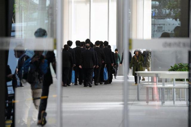 電通本社に強制捜査に入った厚労省の職員ら=2016年11月7日