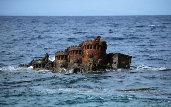 海上に露出する赤くさびた鬼怒川丸の船体の一部=9月3日、ソロモン諸島・ガダルカナル島、橋本弦撮影