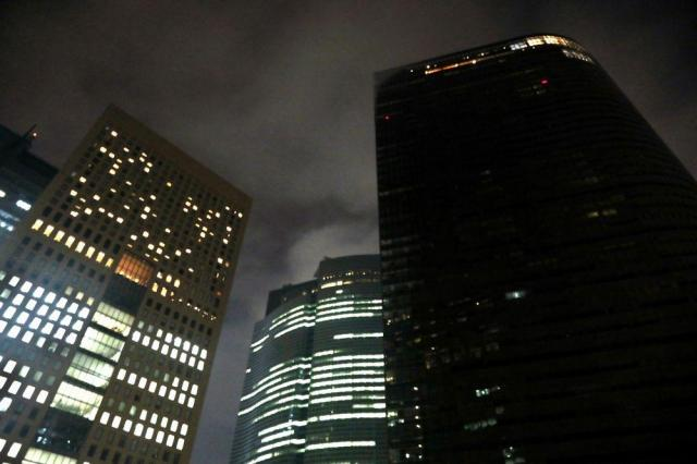 長時間労働の批判を受け午後10時で一斉に消灯された電通本社ビル(右)は=2016年10月25日、東京都港区、林紗記撮影
