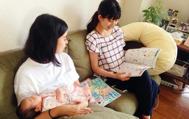 左からコノビー編集部の三輪、維悦さん。育児雑誌を見ながら、ちょっとした相談中。