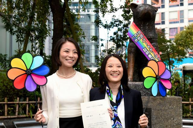 「パートナーシップ証明書」を手に、ハチ公前で取材に応じる増原裕子さん(右)と東小雪さん=2015年11月5日