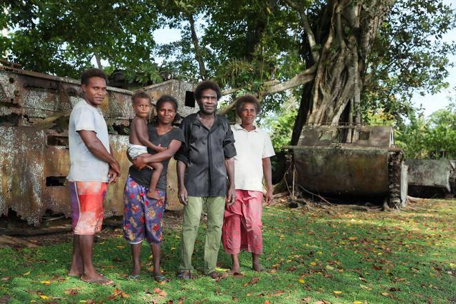 テテレ海岸にある「博物館」を管理するサミュエルさん(右から2人目)とその家族。放置されたアメリカ軍の水陸両用トラクターを親族から引き継ぎ、展示している=ソロモン諸島ガダルカナル島