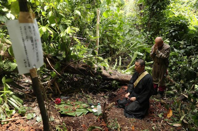 密林の中で見かった日本兵に手を合わせ読経するボランティアら=ソロモン諸島ガダルカナル島