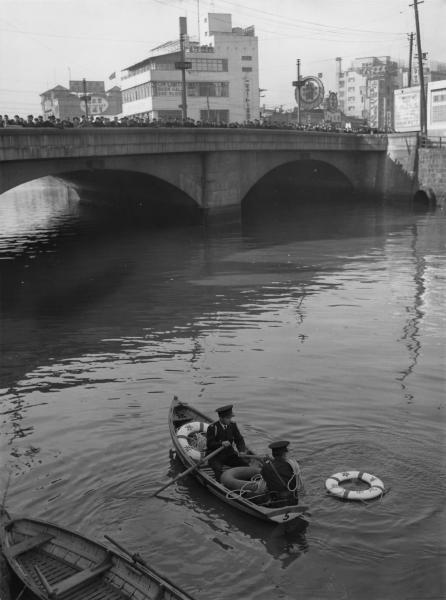 クリスマスの騒ぎで酔った人が川に転落する事態が相次いだ。ボートに乗って警戒する警察官=1953年12月24日、東京・有楽町