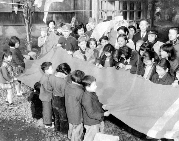 サンタクロースから贈られた長さ13尺の靴下をもつ子どもたち=1955年12月24日、東京都世田谷区