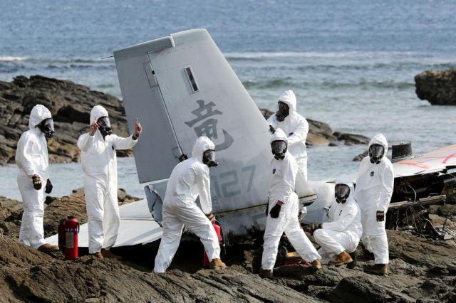 沖縄県名護市の海岸で、浅瀬に不時着して大破したオスプレイの機体を切断する米軍関係者=2016年12月16日、関田航撮影