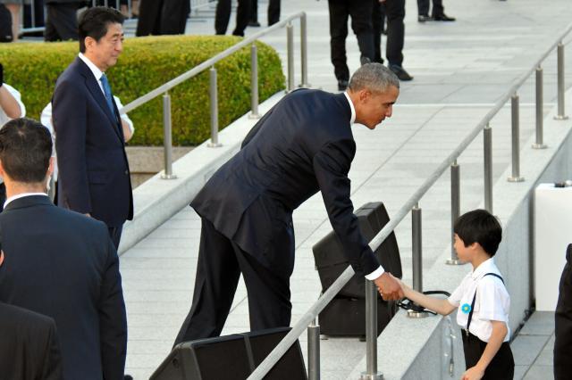 平和記念公園を訪問したオバマ米大統領と握手する長崎市の中学生。左は安倍首相=2016年5月27日、広島市中区、代表撮影