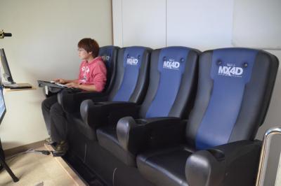 座席の上下左右の動きを、プログラマーが体感しながら調整する=ダイナモアミューズメント