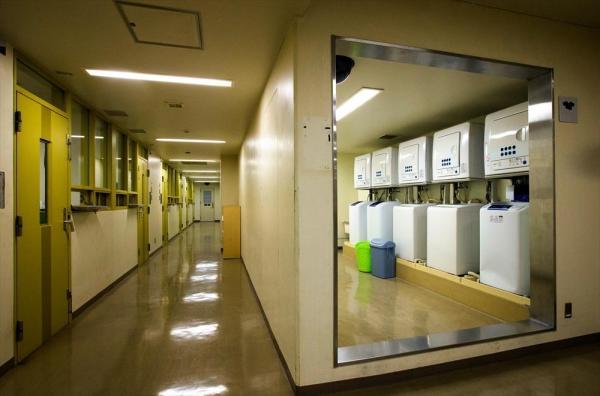 東日本入国管理センターの共用スペース。廊下の右側は洗濯機やシャワー室が並ぶ空間になっている=茨城県牛久市、鬼室黎撮影